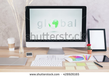 Global network concept with computer monitor on creative designer desk with coffee cup, electronic devices, stationery items and blank picture frame. Mock up